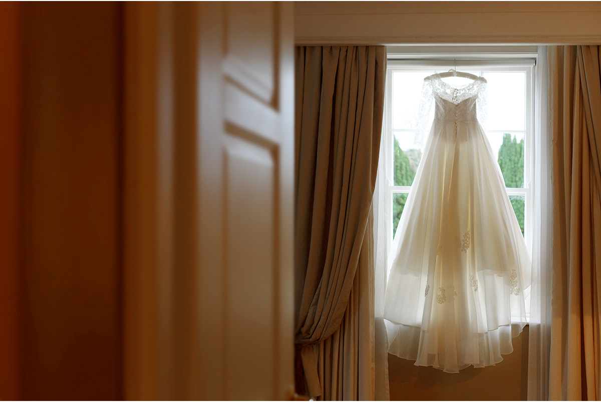 wedding dress hanging from window