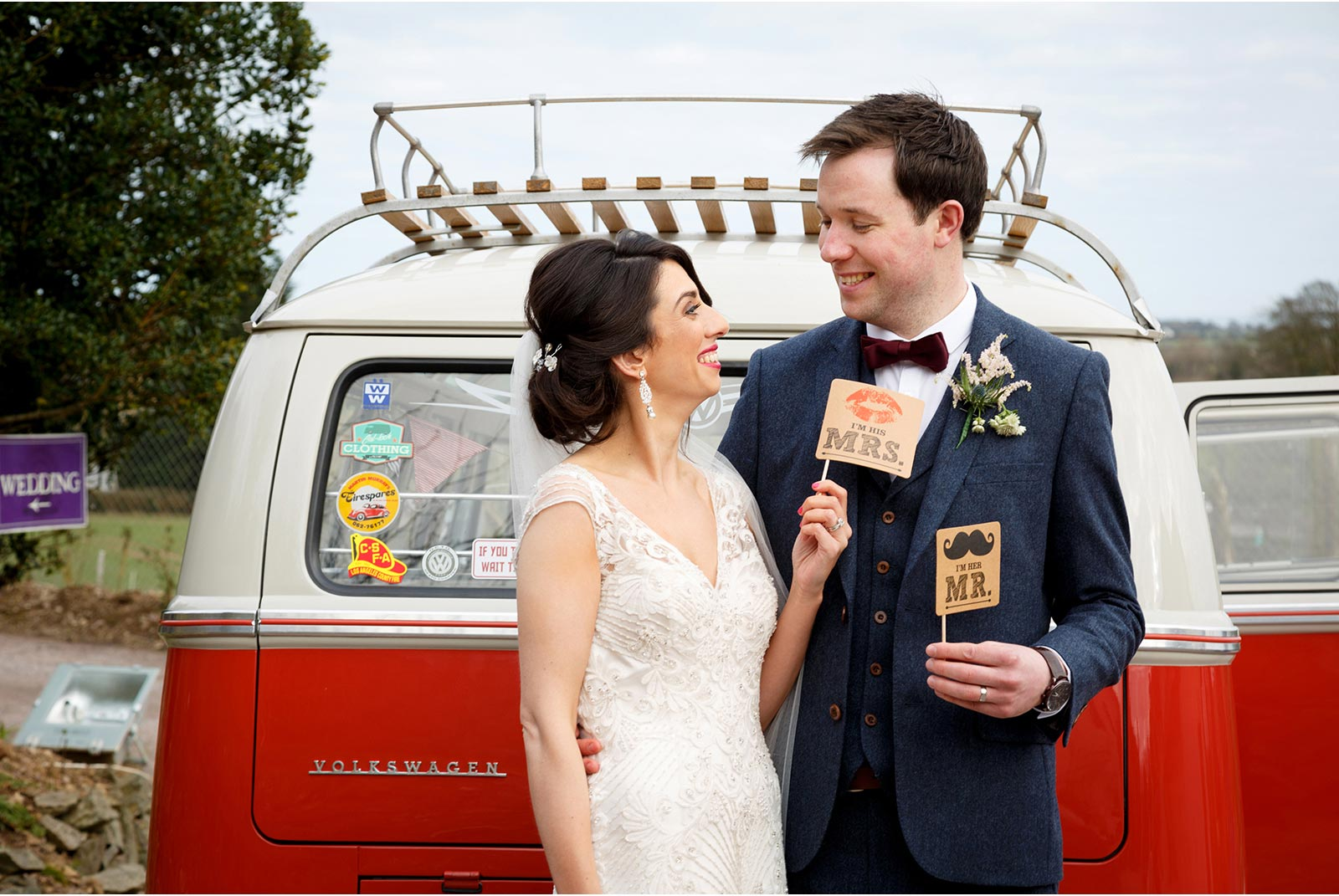 couple pose at their red VW camper van