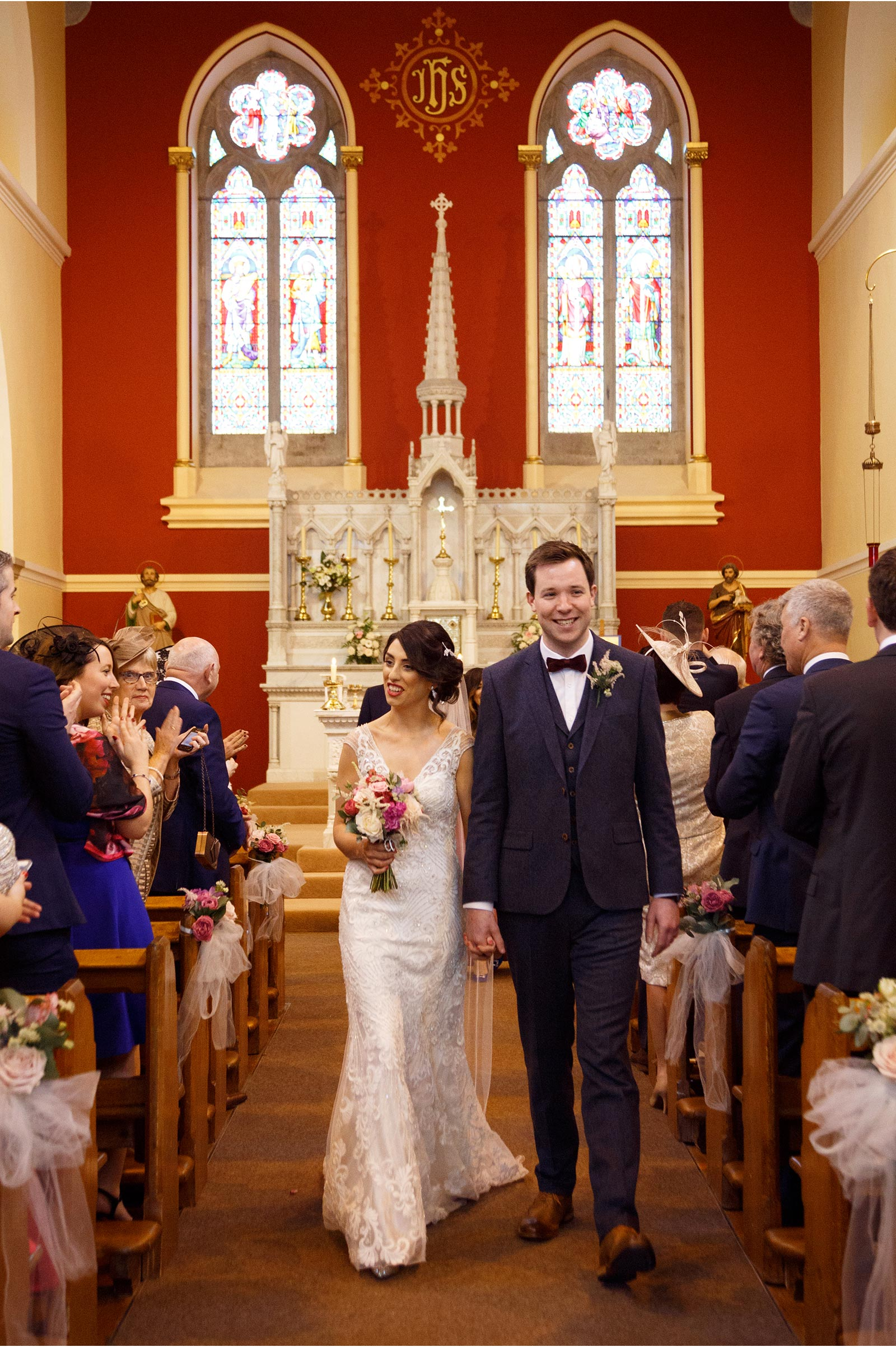 couple walk down the isle of the church