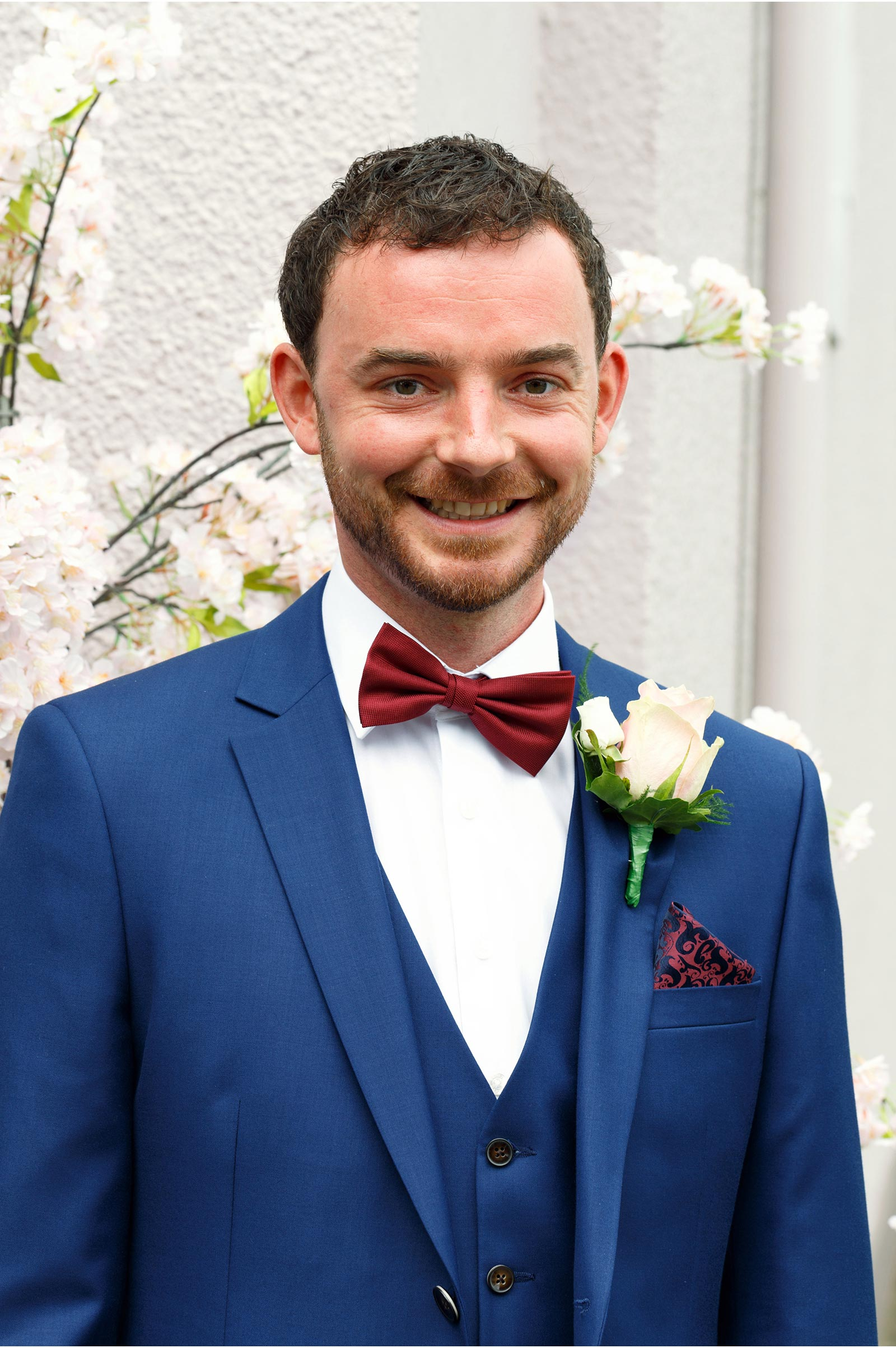 groom in navy blue suit with wine bowtie