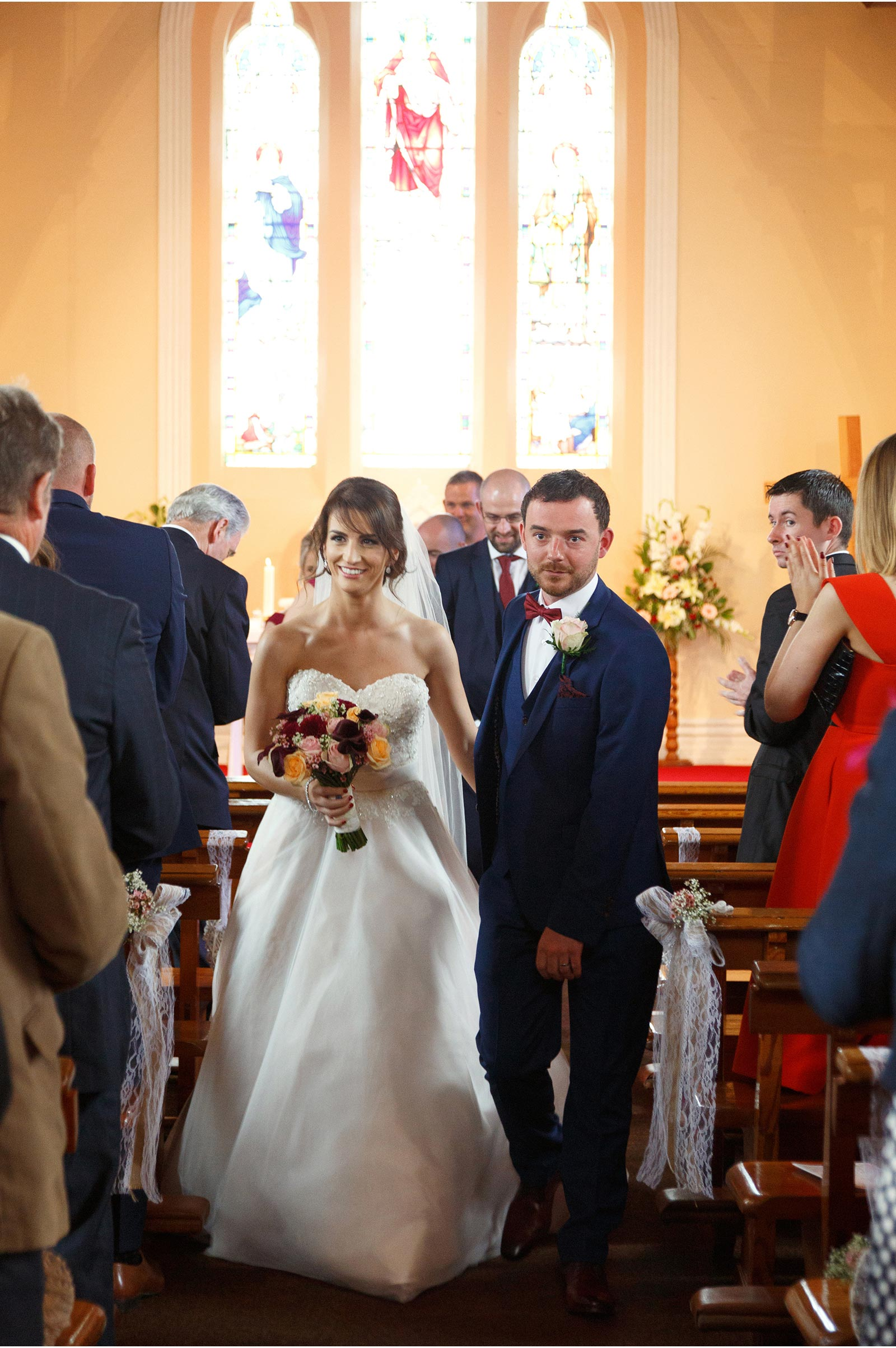 couple walking down the isle in Kilflynn church