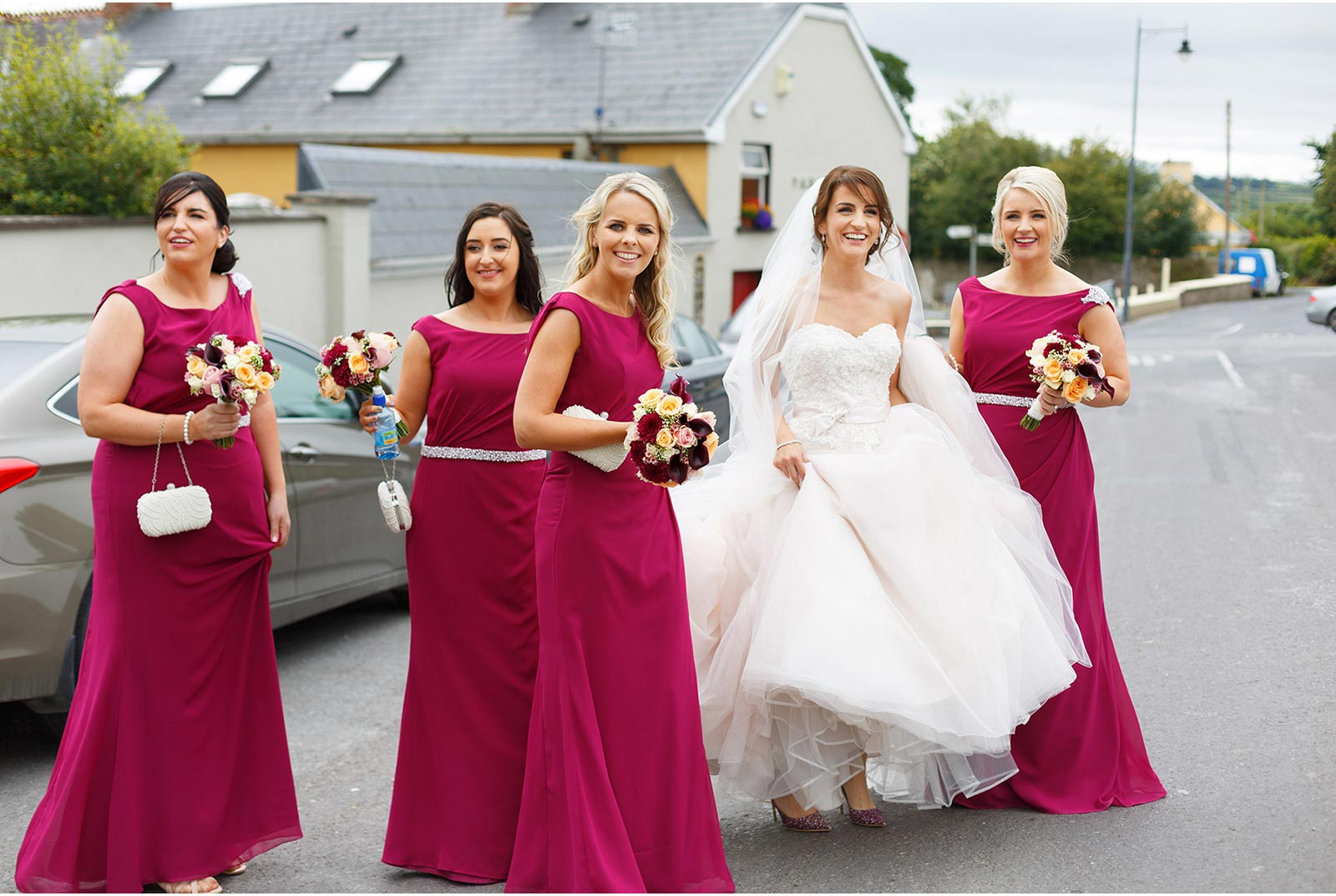 girls making their way down the street to the pub after the wedding