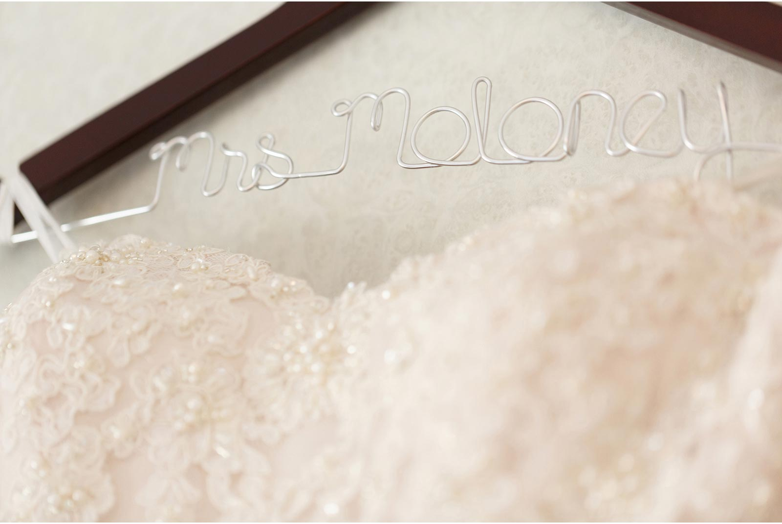 Brides gown hangs on a hanger with her married name