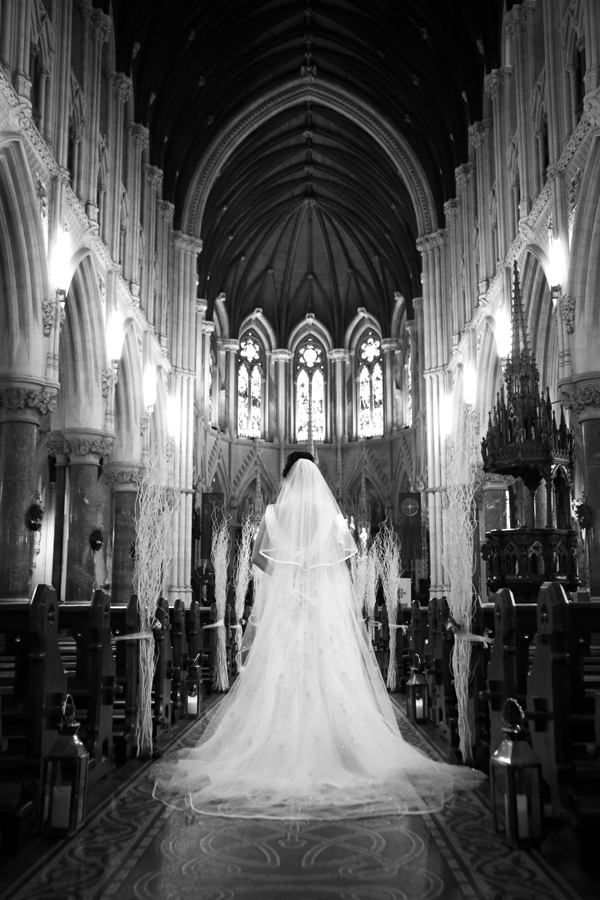 Bride stands in the isle of Cobh Cathedral