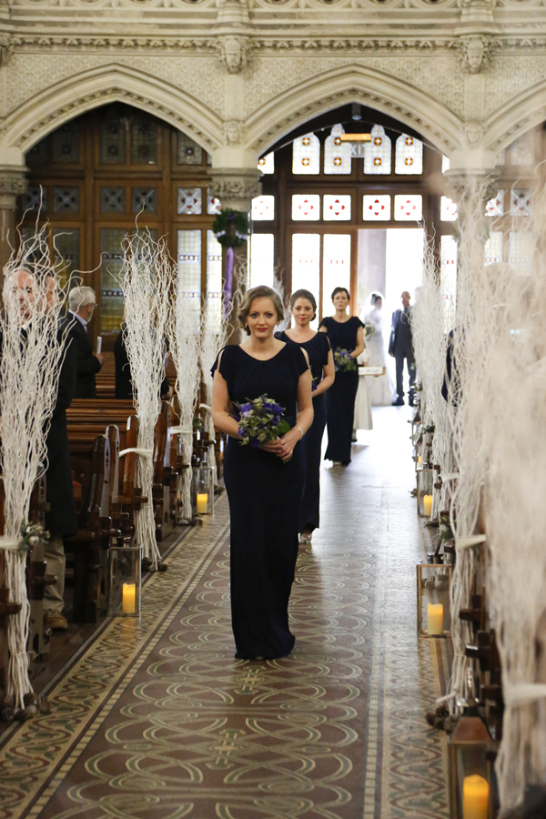 Brides maids walk up the isle of Cobh Cathedral which is decorated festively