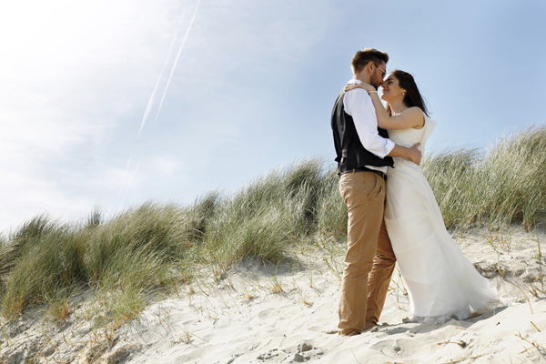Bride and groom kiss in the sand dunes of Inchydoney, West Cork