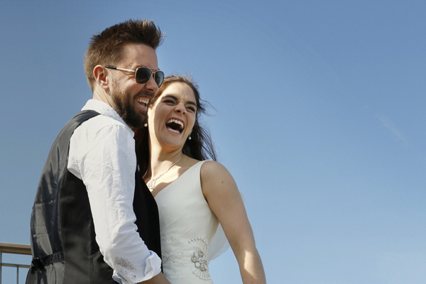 Bride and groom laughing against a blue sky