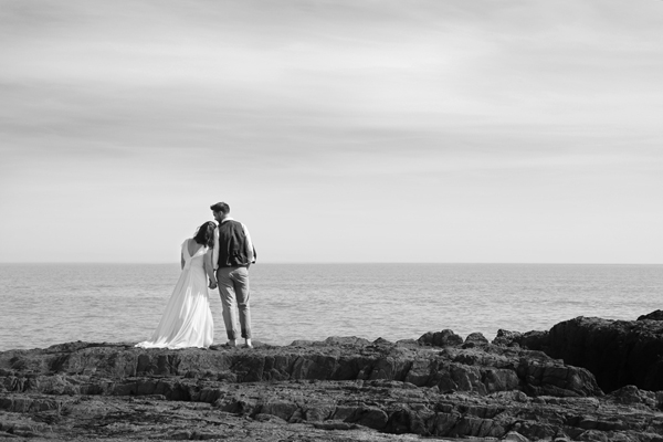 wedding couple stand admiring the ocean at Inchydoney, West Cork