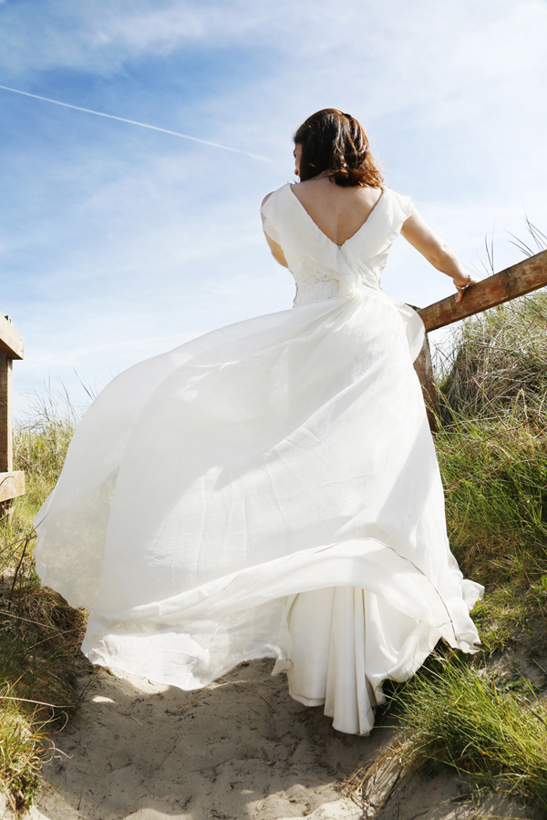 Brides wedding dress billowing in the wind at Inchydoney