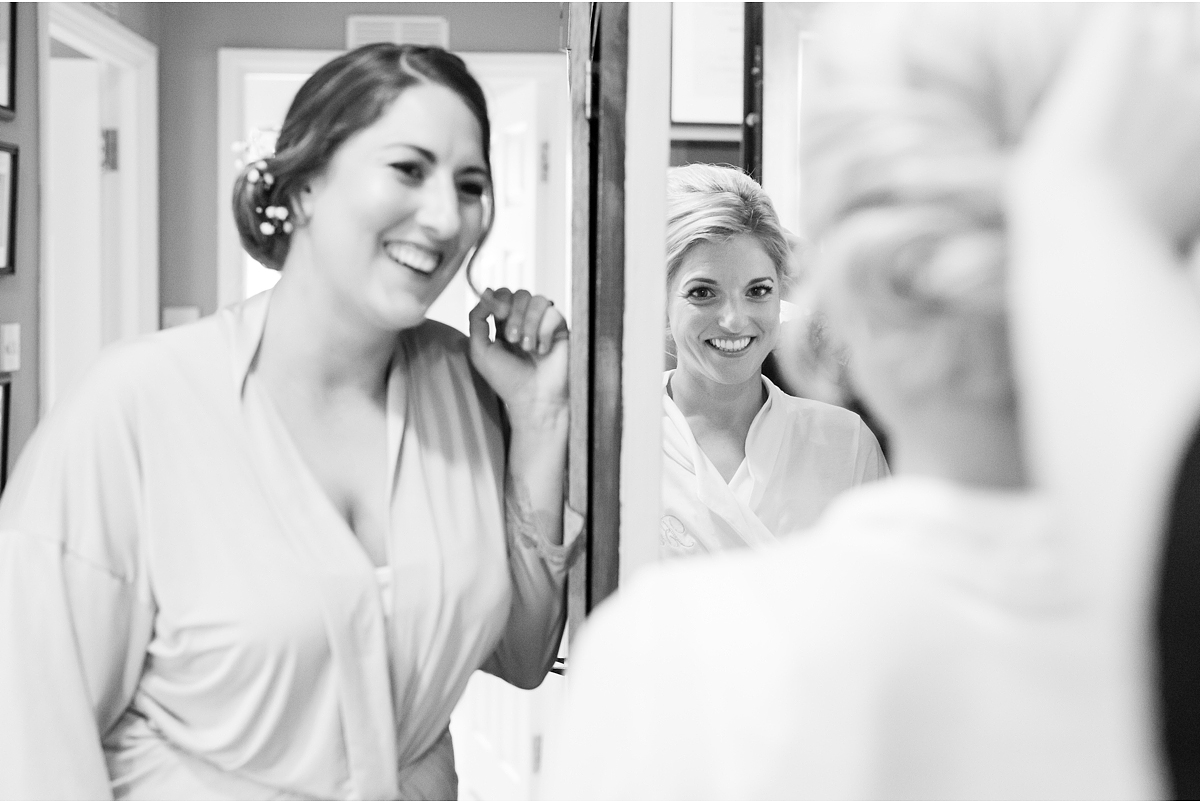 black and white photo of bride getting ready and sister looking on smiling