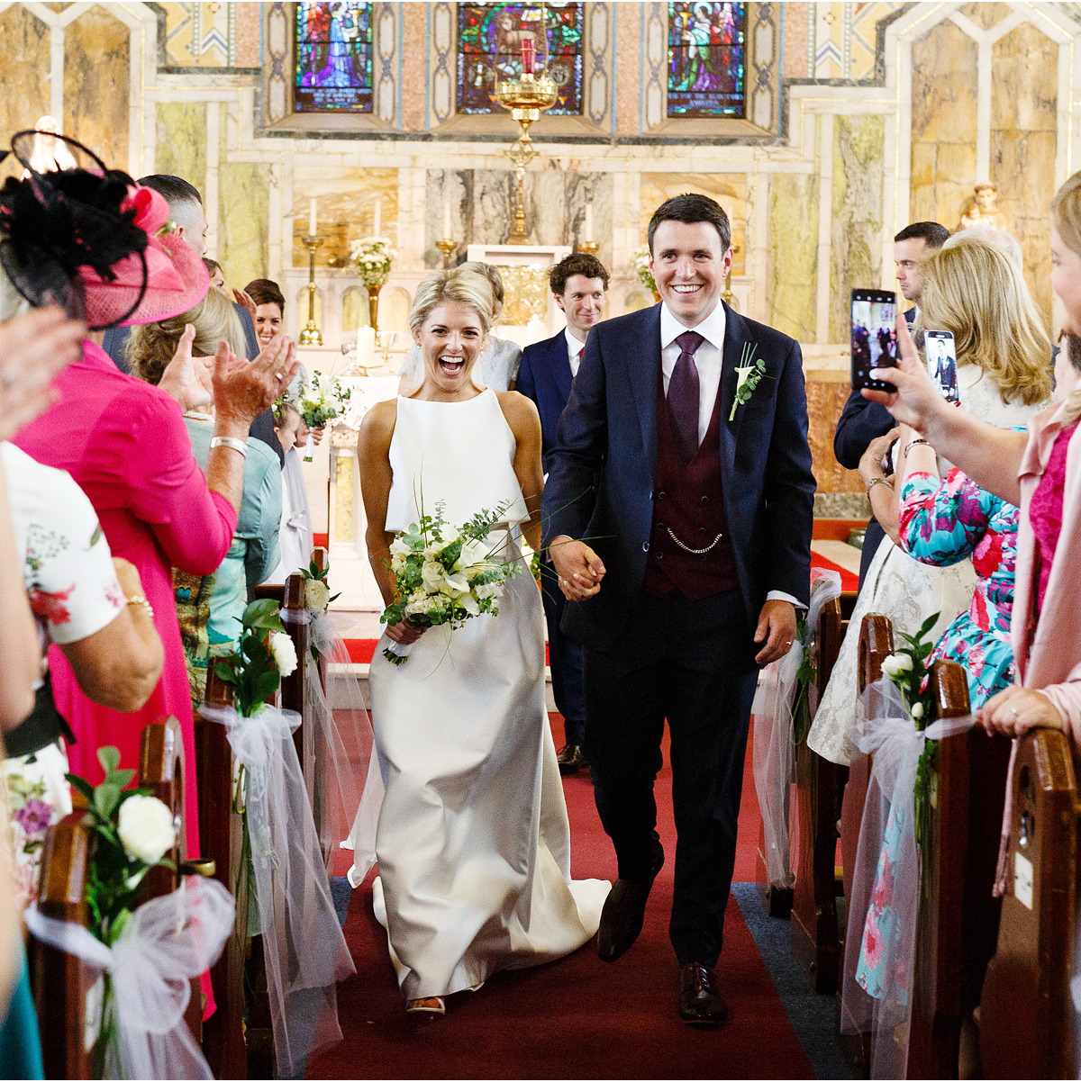 newly married couple walk down the isle together