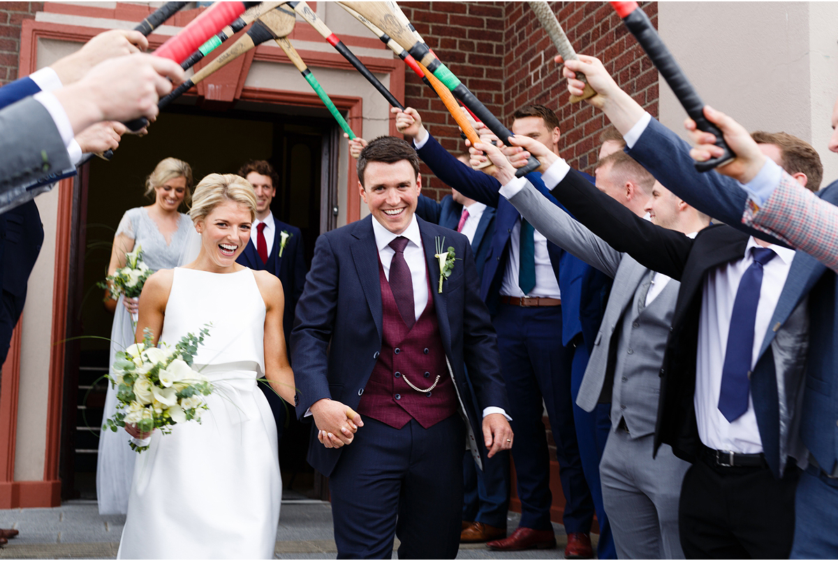 bride and groom exit church under hurley guard of honour