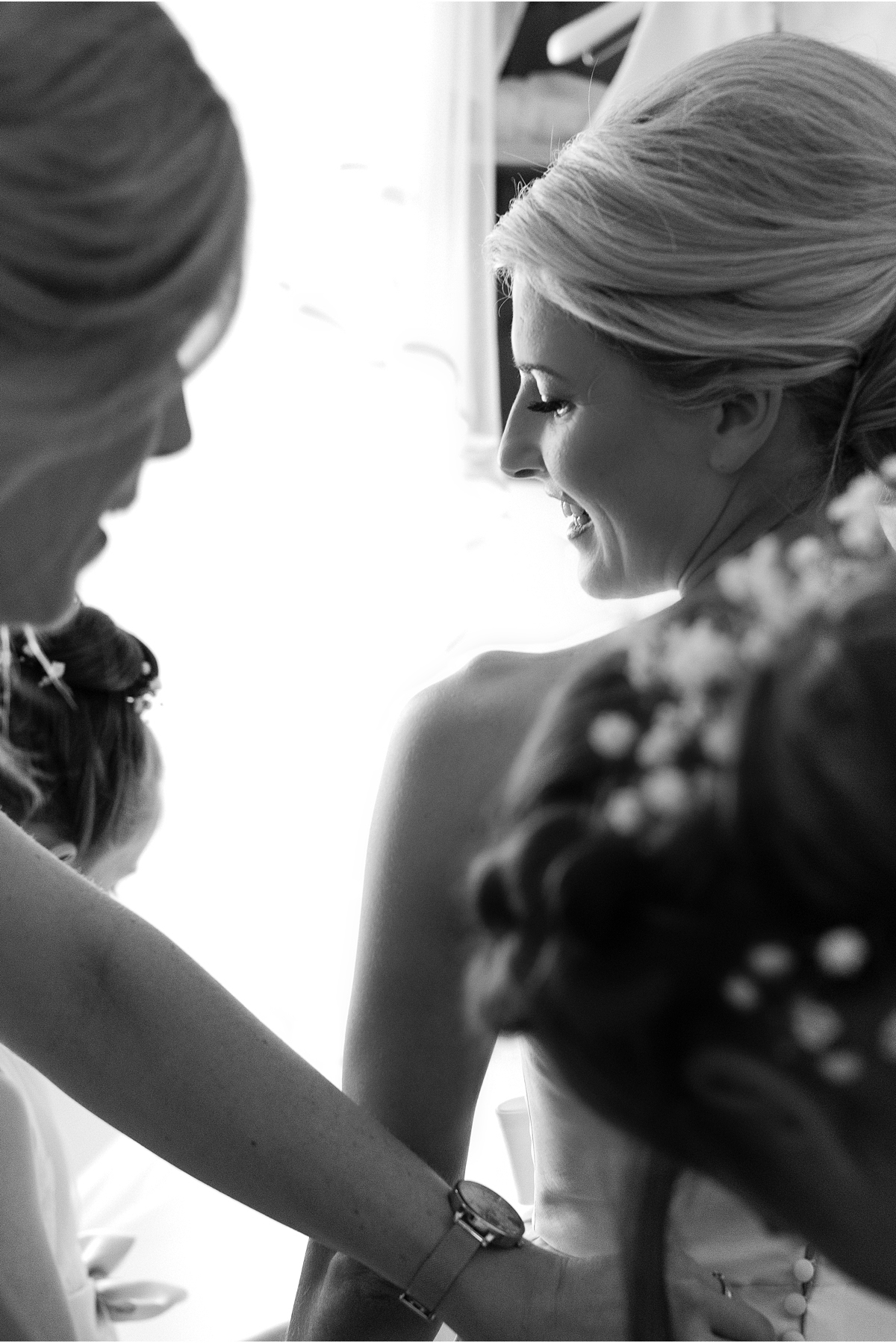 black and white photograph of bride getting dressed