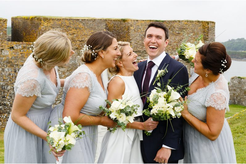 groom surrounded by brides maids all laughing