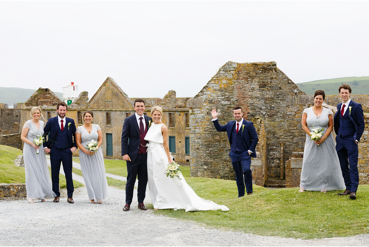 wedding party spread out a bit in the grounds of Charles Fort overlooking Kinsale