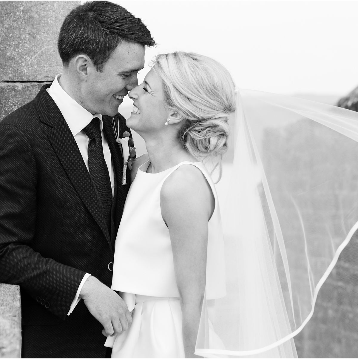 black and white photo of bride and groom nose to nose with brides veil blowing in the wind