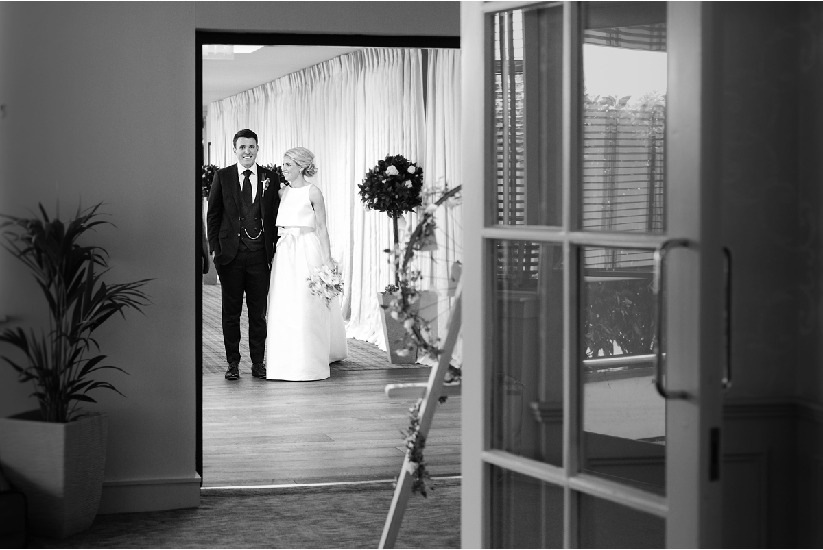 bride and groom wait outside dining room before being announced to the crowd