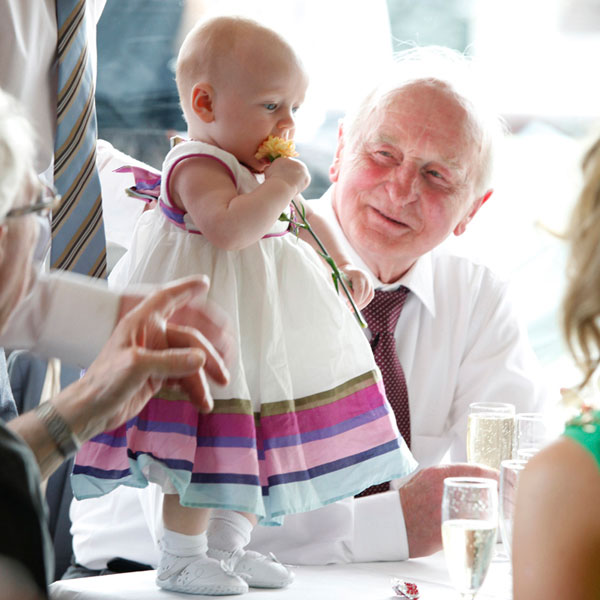 toddler eating a flower as grandad looks on