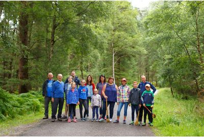 3 generations of a family line up casually across a path in the midle of the Gougane Barra foret park, some of them hold their hurleys - portrait photogapher Cork