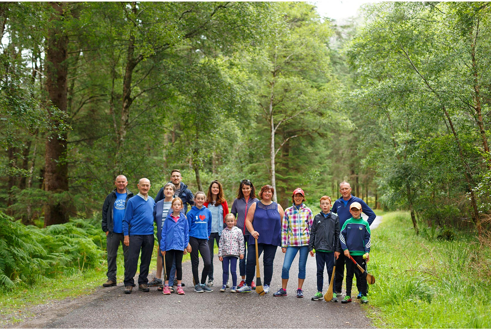 3 generations of a family line up casually across a path in the midle of the Gougane Barra foret park, some of them hold their hurleys