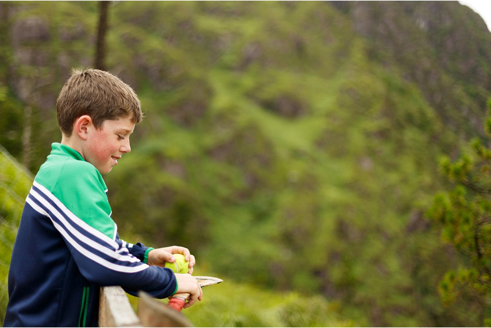 Young Irish lad has tenis ball and hurley in the hills of Gougane Barra