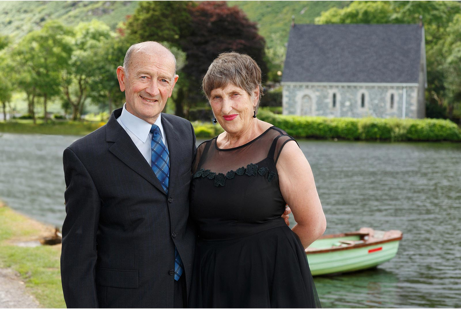 Smartly dressed couple pose at Gougane Barra celebrating 50 years of marriage