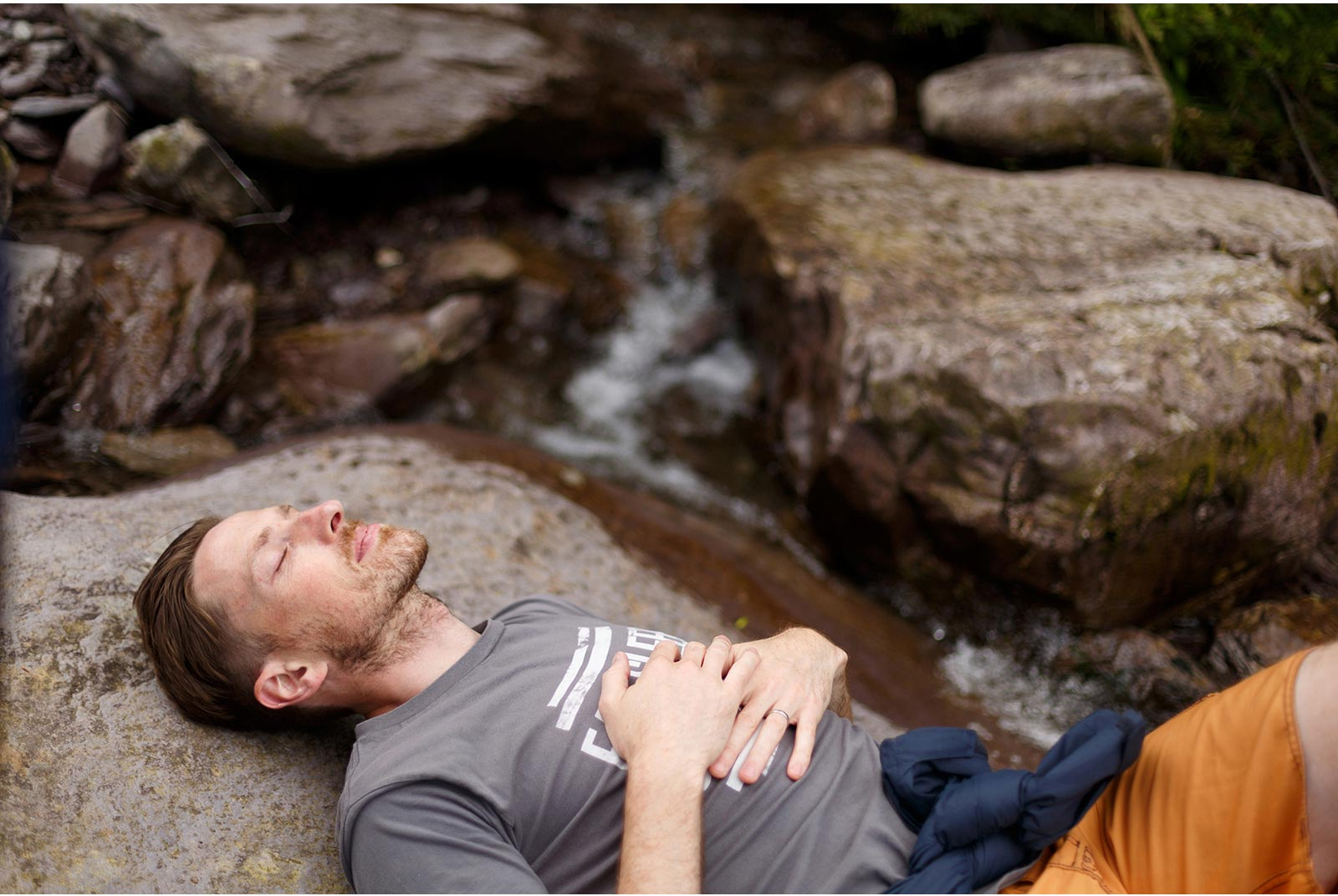 Man lies on his back meditatively on the rocks at the rivers edge at Gougane Barra forest park
