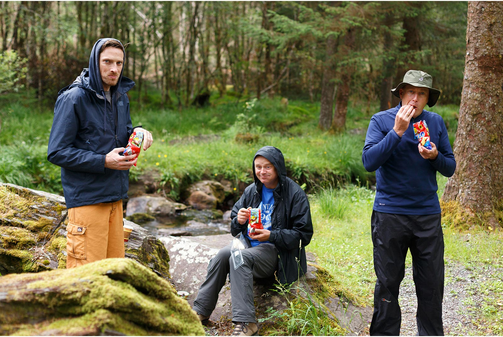 3 guys eating packets of tayto crisps in the rain. A typical Irish picnic scene.