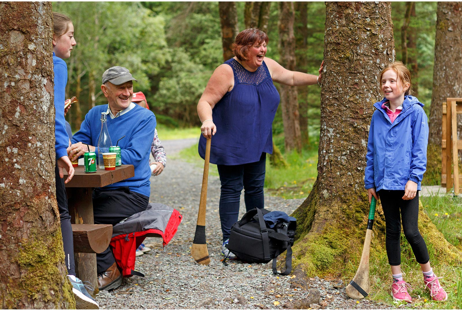 3 generations of the family share a laugh during a picnic in the forest