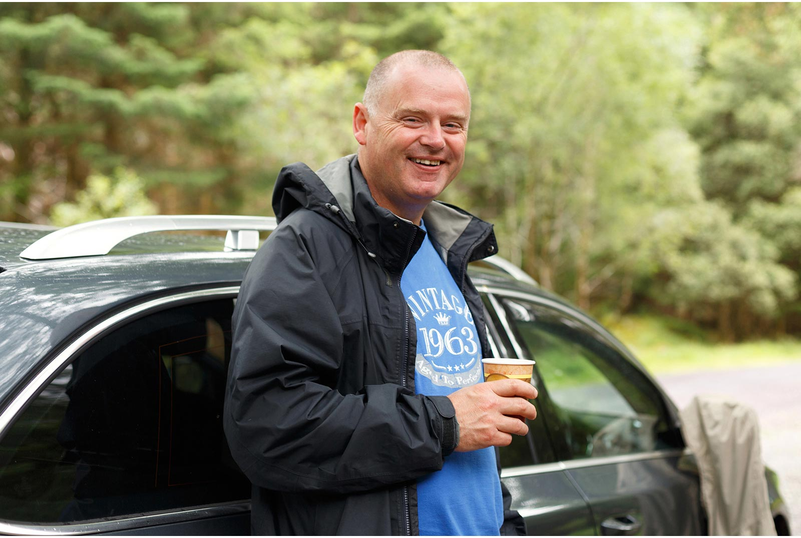 Man enjoys a cup of tea while resting against his car in the Irish forest