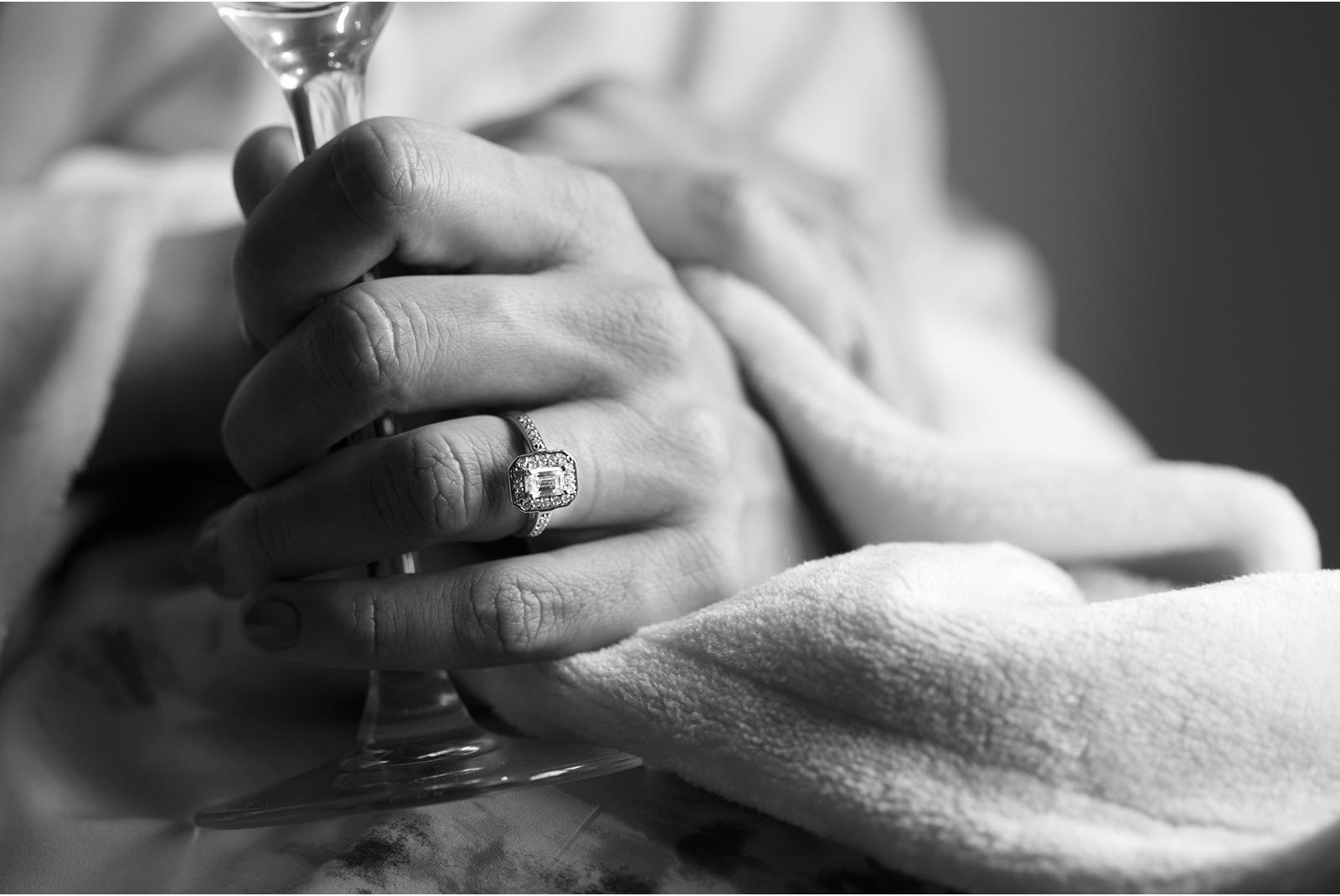 Bride holds champagne flute displaying vintage style engagement ring