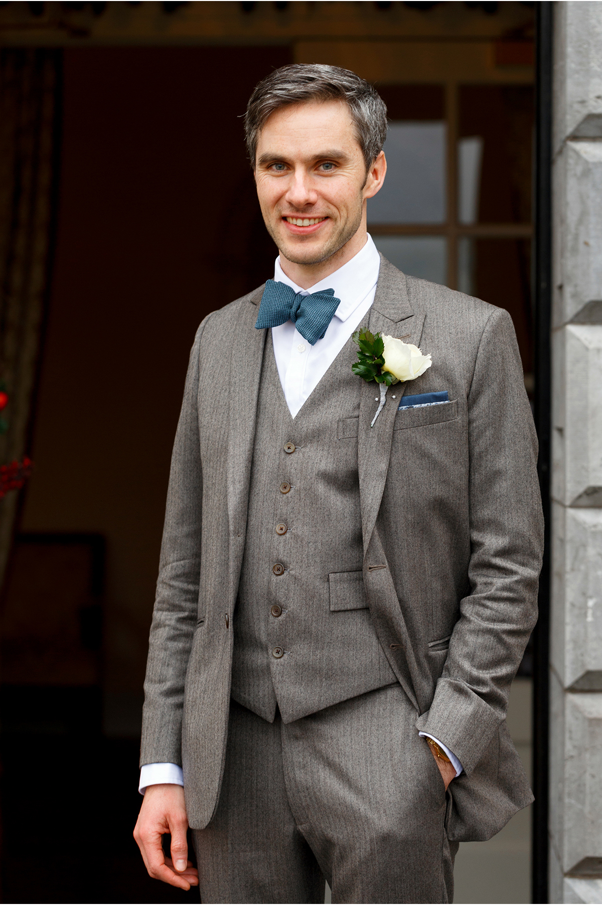 handsome groom in tweed and teal bowtie