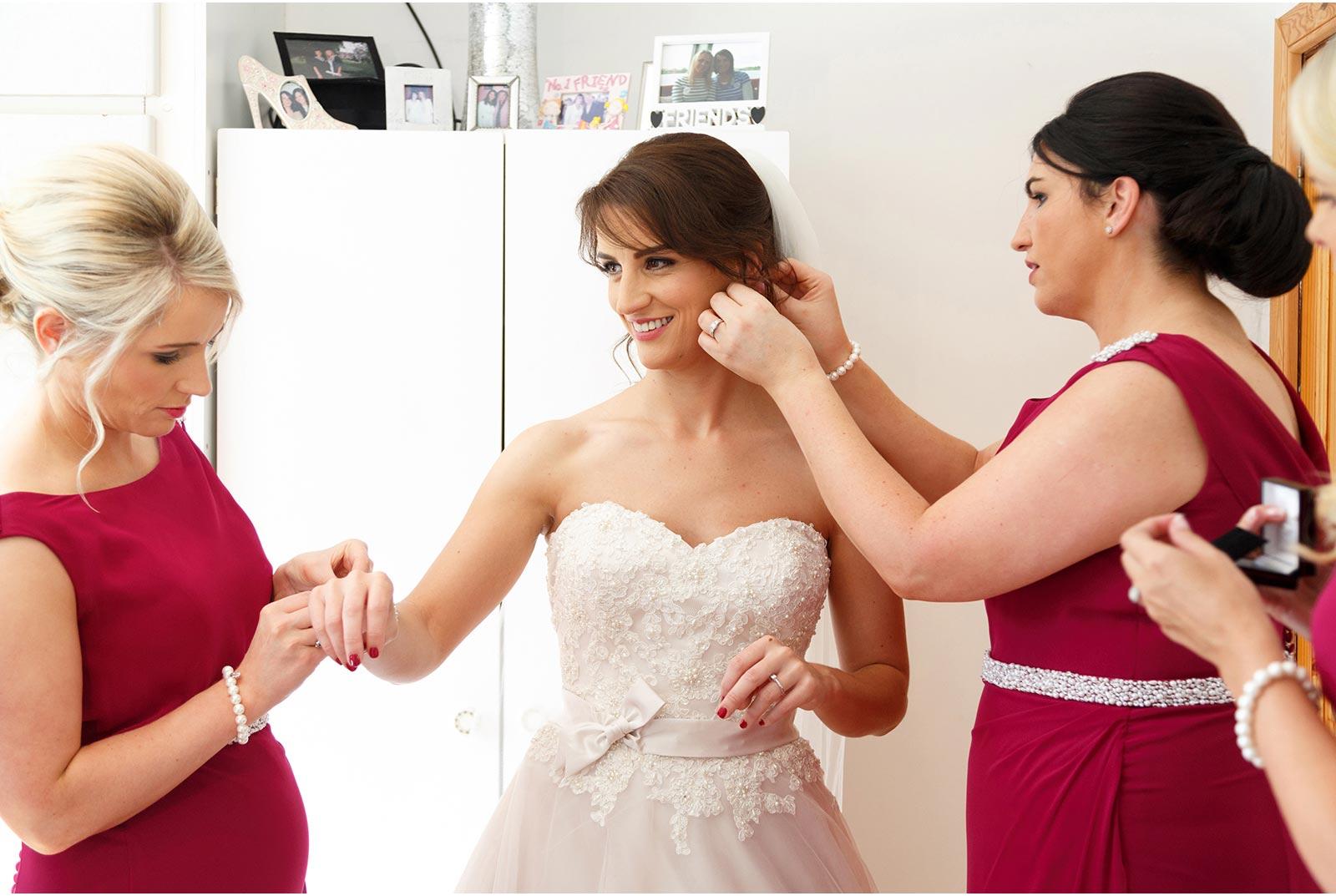 bridesmaids dressing bride
