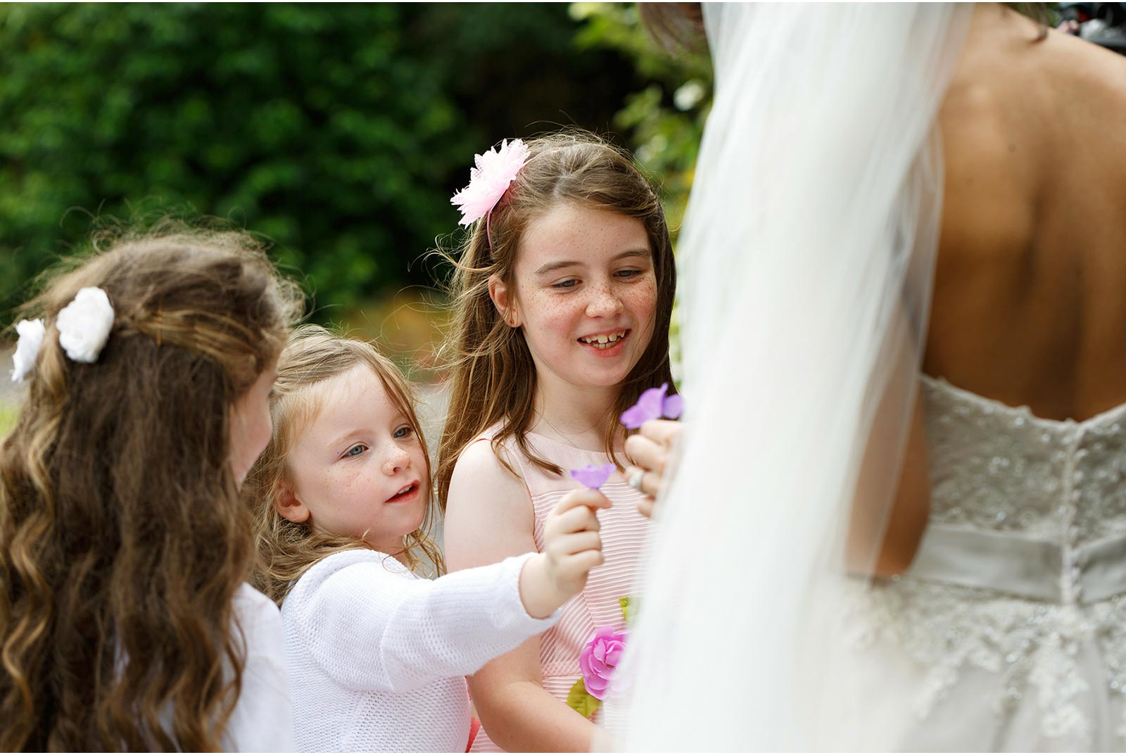 cute little girls pick flowers and present them to the bride