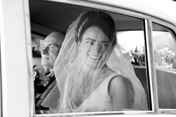 Bride and her dad in the wedding car with veil over her face taken by Cork wedding photographer Claire O'Rorke