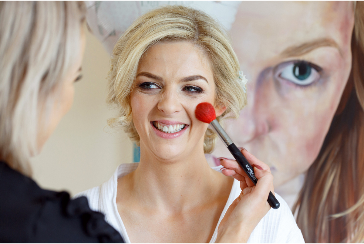 candid wedding photograph of bride getting make up done