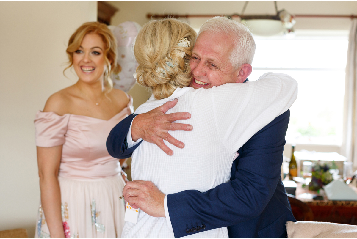 candid wedding photograph of bride and father hugging