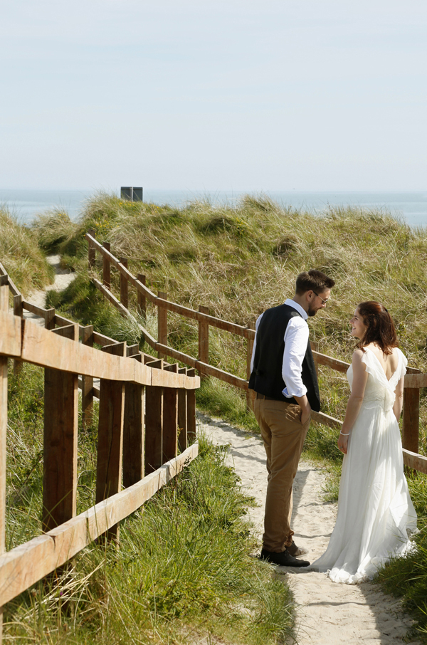 Bride and groom standing on a sandy path to Inchydoney beach