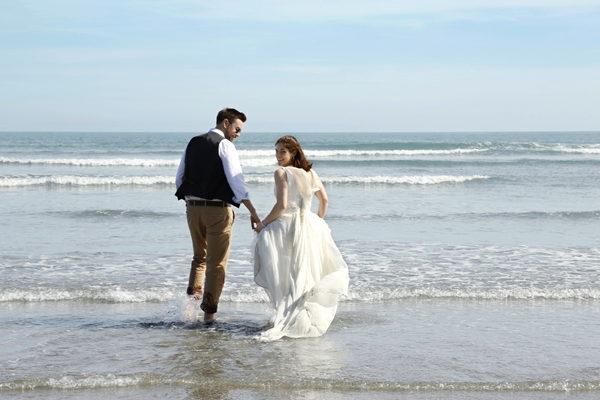 Bride looks over her shoulder as she and her husband run into the sea