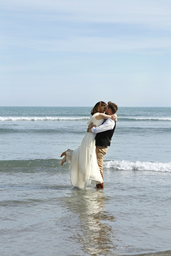 Groom holds bride aloft and kisses her, while standing in the sea