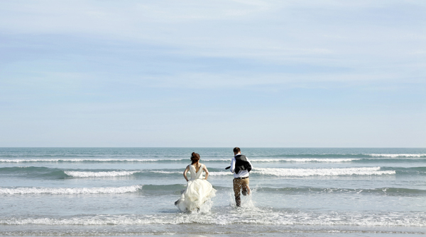 Bride and groom running into the sea at Inchydoney, West Cork