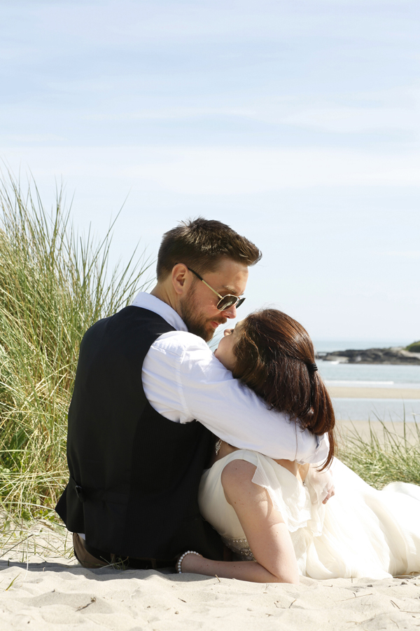 Groom holds the bride in an embrace at Inchydoney beach