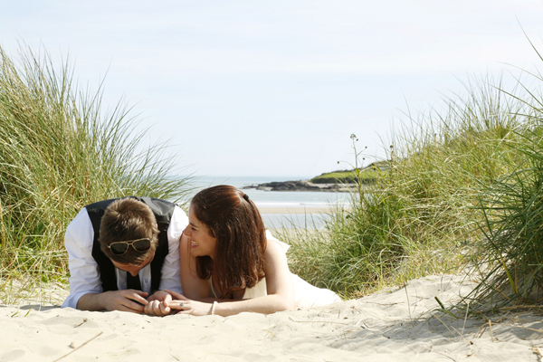 Bride and groom share a giggle on the beach