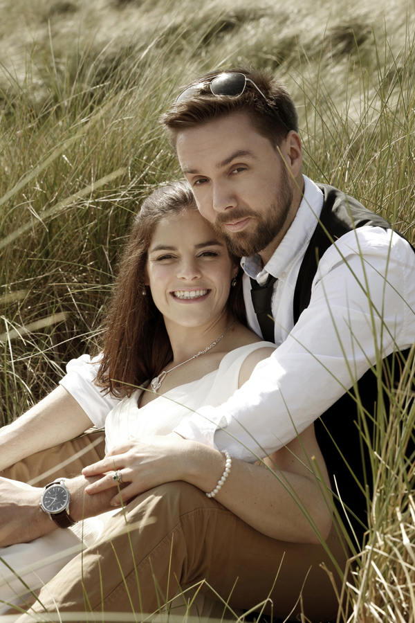 Bride and groom sit together in the sand dunes at Inchydoney