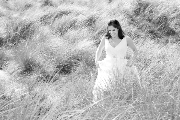 Bride walks through the rushes in the sand dunes at Inchydoney, West Cork