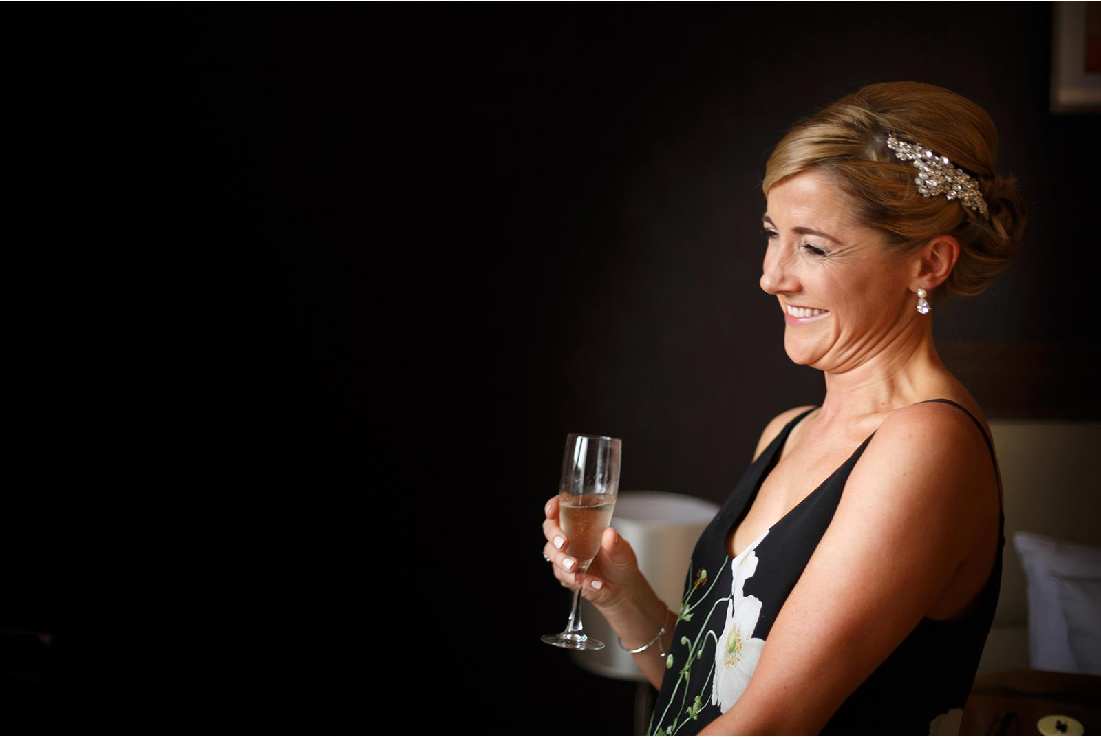 bride enjoying preperations with a glass of champagne