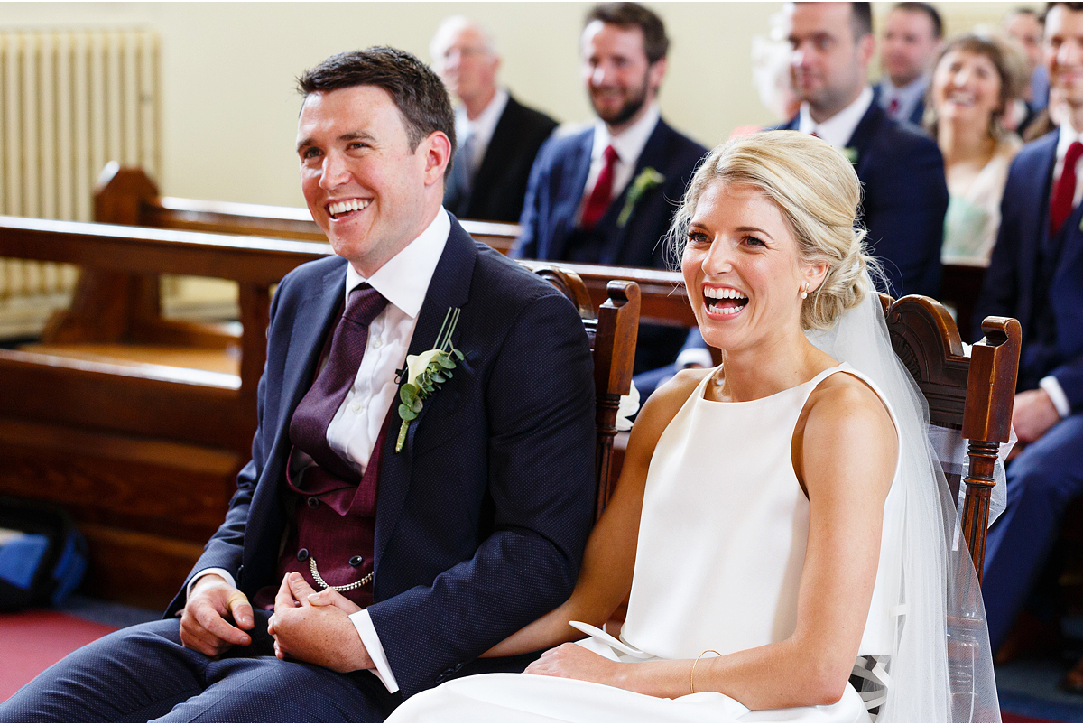 bride and groom laughing at something priest just said
