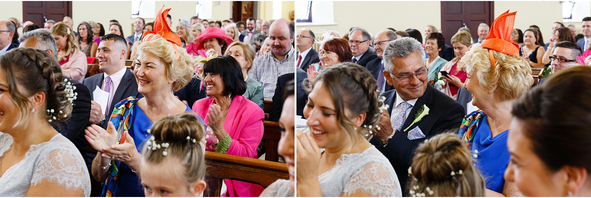 mother and father of the bride exchange a happy proud look while applauding newly married couple