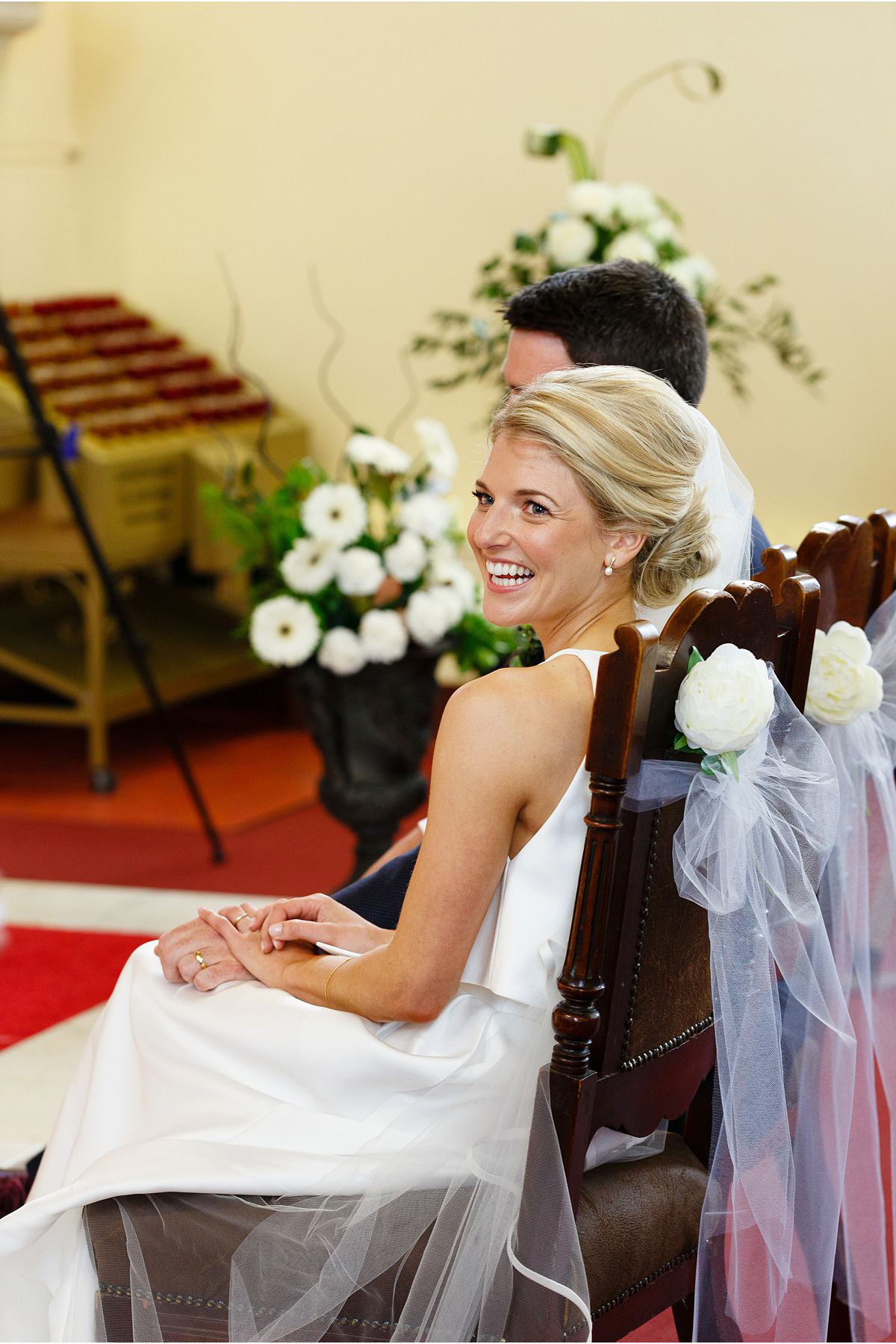 beaming bride glances over her shoulder during wedding cerrmony