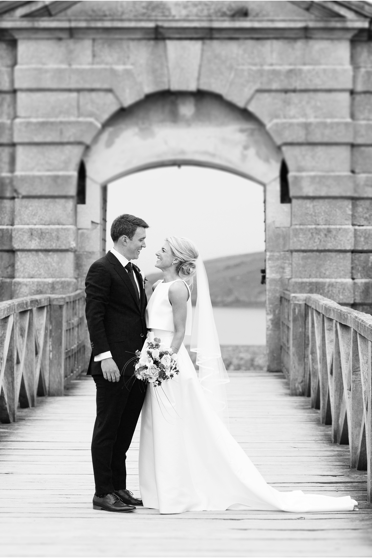 black and white full length portrait of bride and groom on board walk to Charles Fort entrance, Kinsale